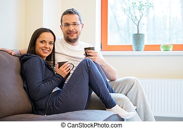 Young cheerful couple on a sofa in home interior