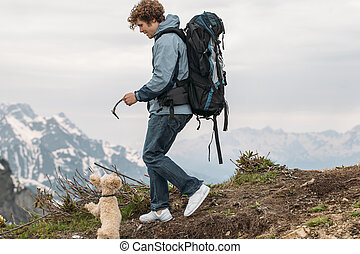 cheerful explorer with a stick entertaining his dog while walking on the hill