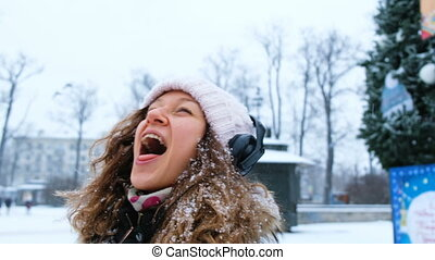 Young cheerful girl catches snowflakes with his mouth in a Park with headphones closeup.