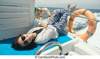 Young cheerful girl is having cruise on board of a yacht in the open ocean. Smiling woman is lying on deck of a little ship in the sea with her legs in the air between two orange life-buoy rings.