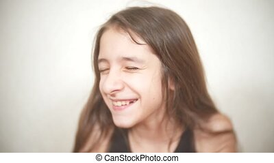 Young cheerful girl looks at the camera. smile closeup
