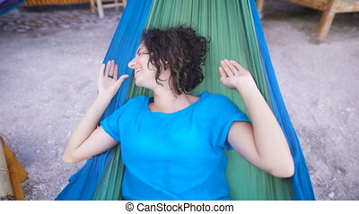 Young cheerful girl lying in hammock on tropical beach, hiding her face and laughing happily. Adorable woman in blue dress is smiling and relaxing in tissue swing in ithe bar of Bali island.