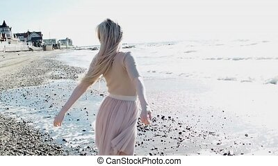 Young cheerful girl on the seashore. Young blonde woman smiling. Open arms hugs the ocean