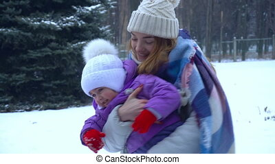 young cheerful girl throws the baby in her arms on the street in winter