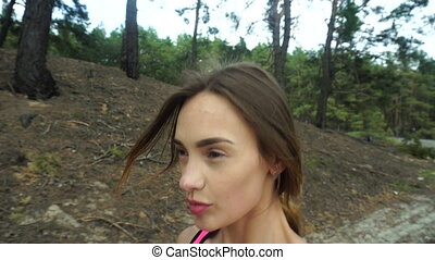 young cheerful girl walks around the forest