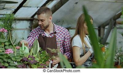 Young cheerful man in apron watering plant and chat with woman in gloves loosen ground in flowers in greenhouse