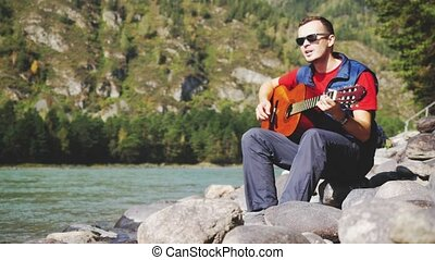 Young cheerful man wearing sunglasses plays on a guitar...