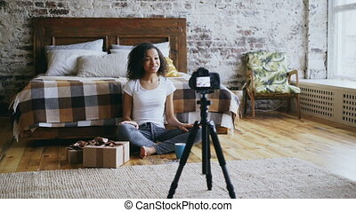 Young cheerful mixed race girl recording video blog about packing christmas gift box at home
