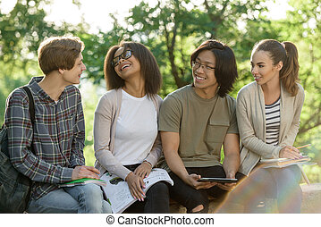 Young cheerful students sitting and studying outdoors