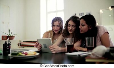Young cheerful teenage females friends sitting indoors,...