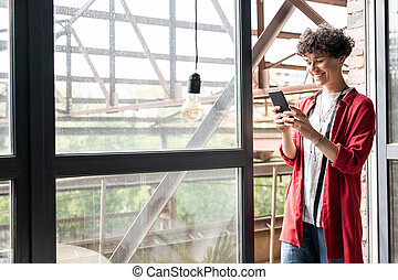 Young cheerful woman in casualwear standing by open window and using smartphone
