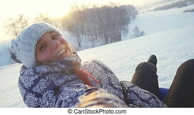 Young cheerful woman is sledding from the mountain through the snow in slow motion during beautiful sunset. 1920x1080