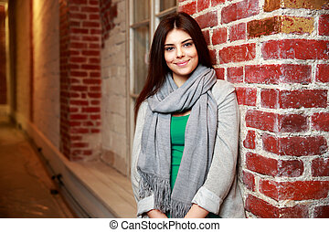Young cheerful woman leaning on the brick wall