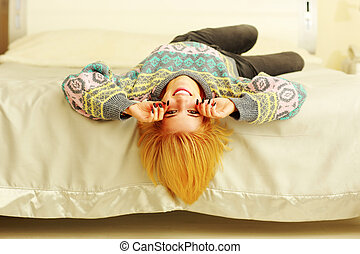 Young cheerful woman lying on the bed at home