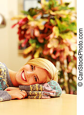 Young cheerful woman lying on the table at home