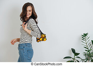 Young cheerful woman posing with a net bag containing about a kilo of mandarins.