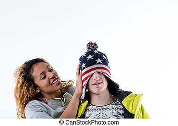 Young cheerful woman putting cap on man head