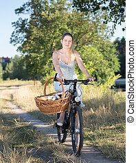 Young cheerful woman riding bicycle with basket