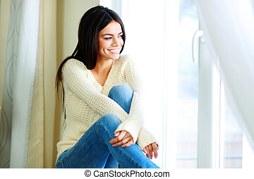 Young cheerful woman sitting on a window-sill and looking ...