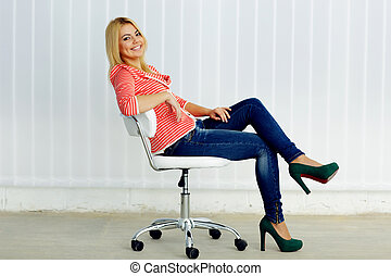 Young cheerful woman sitting on the modern chair in office