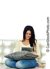 Young cheerful woman sitting on the sofa and using tablet computer