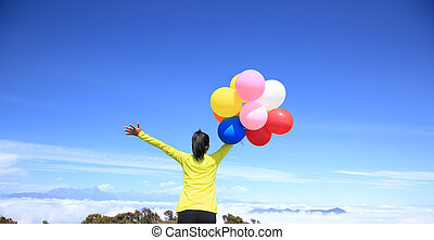 young cheering woman running with colorful balloons on mountain peak