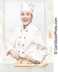 young chef cutting blue cheese in kitchen