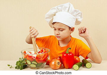 Young chef mixing the vegetables in bowl with salad