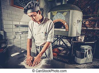 Young chef preparing dough
