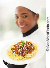 young chef presenting spaghetti dish