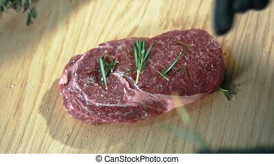 Young chef sprinkles beef steak with rosemary in kitchen of restaurant.