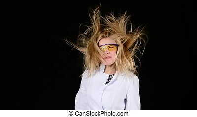 Young chemist blond hair dryer dries hair super on black. Slow motion