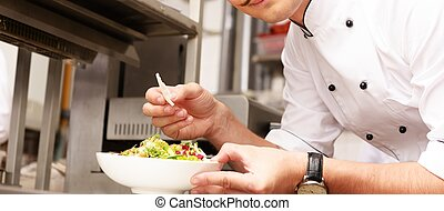 Young chief cook with gourmet food on kitchen in restaurant