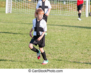 Young child boy playing soccer