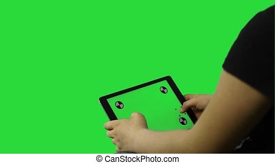 young child boy works on tablet on the table - green screen