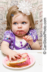 Young child celebrating her first birthday - Girl eating a...