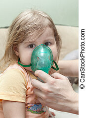 Young child doing inhalation with nebulizer at home. Mother hands holding mask