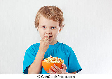 Young child eating popcorn on white background