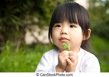 Young child holding a plant in her