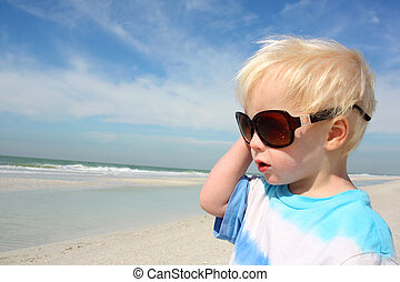 Young Child in Sunglasses Looking at the Ocean