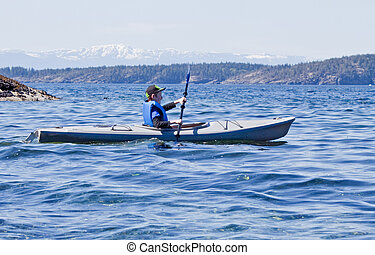 young child kayaking on ocean.