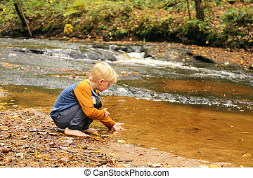 Young Child Playing in River Near Waterfall in Forest