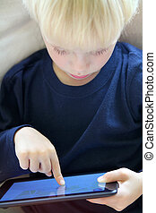 Young Child Playing Internet Game on Computer Tablet - a...