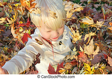 Young Child Playing Outside with Fallen Autumn Leaves