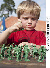 Young child playing soldiers and armies outside in the summer