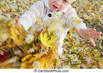 Young Child Playing with fallen leaves in Autumn