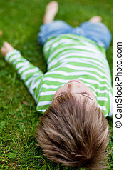 Young child relaxing on green grass
