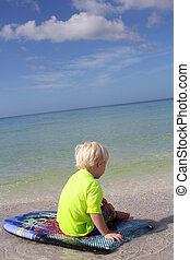 Young Child Sitting on Boogie Board in Ocean