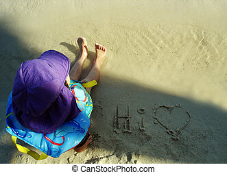 Young child sitting on the sand at the beach