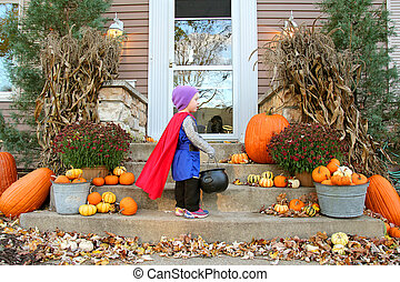 Young Child Standing at House Trick-or-Treating on Halloween...